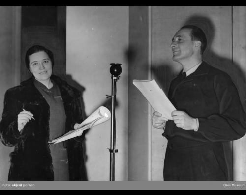"""Tore Segelcke og Harald Schwenzen stående ved en mikrofon under innspillingen av """"Victoria Regina"""" i Radioteatret, ca. 1940."""