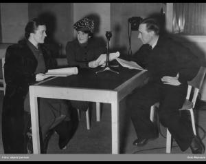 """Tore Segelcke, Gerda Ring og Harald Schwenzen sittende ved et bord under innspillingen av """"Victoria Regina"""" i Radioteatret, ca. 1940."""
